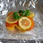 butter, tomatoes, basil, lemon slices and potatoes on aluminium foil