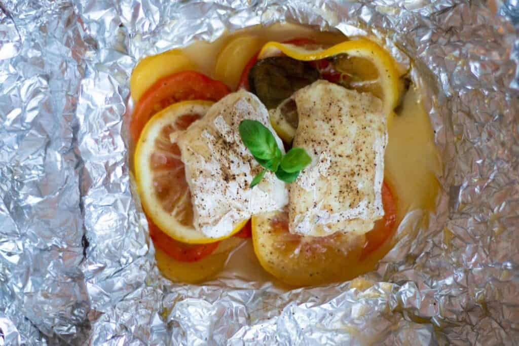 cooked cod in foil packet with tomatoes, potatoes, lemon and basil