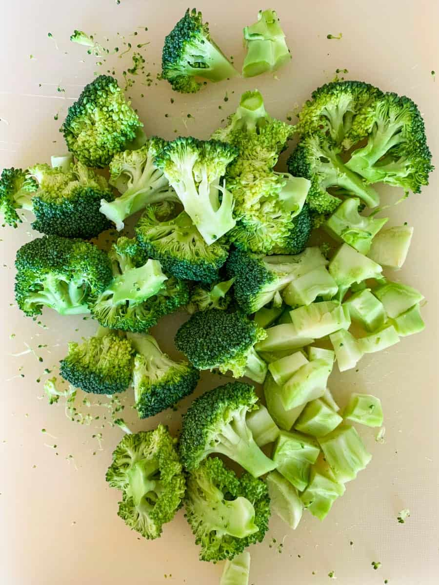 broccoli florets and peeled and chopped broccoli stem on a white chopping board, for one-pan fish & broccoli in lemon butter caper sauce