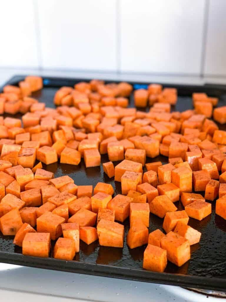 cubes of sweet potato mixed with olive oil, salt and pepper on an oven tray