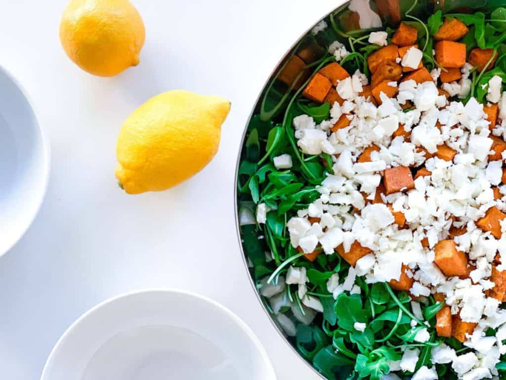 top view of arugula, roasted sweet potato and feta cheese in a large bowl with two empty white bowls next to it