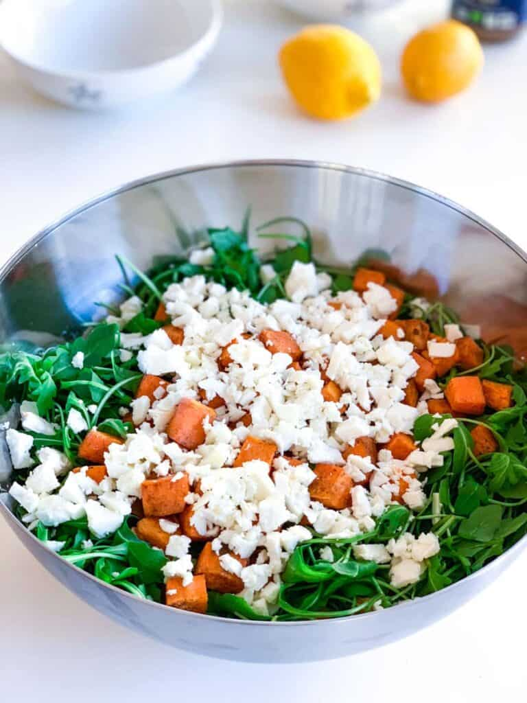top view of arugula, roasted sweet potato and feta cheese in a large bowl with two lemons in the background