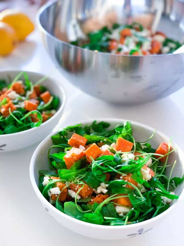 two bowls with roasted sweet potato & feta cheese salad in front of a large bowl containing the same