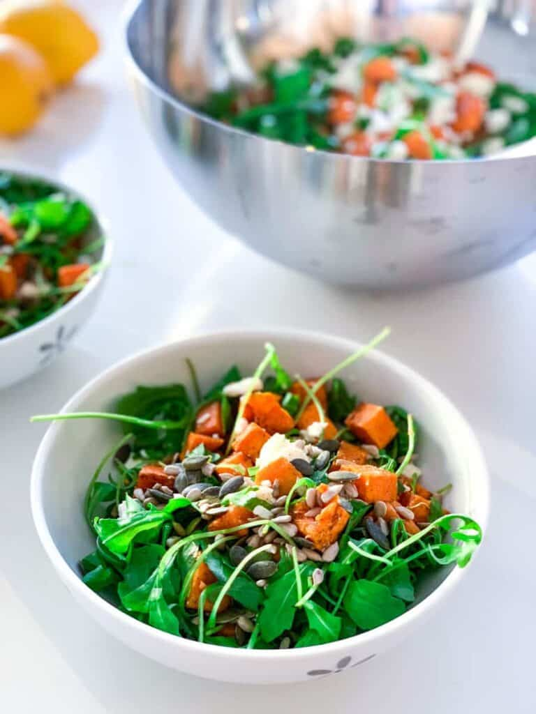 roasted sweet potato and feta cheese salad with arugula and tahini sauce topped with pumpking seedsand sunflower seeds in a white bowl