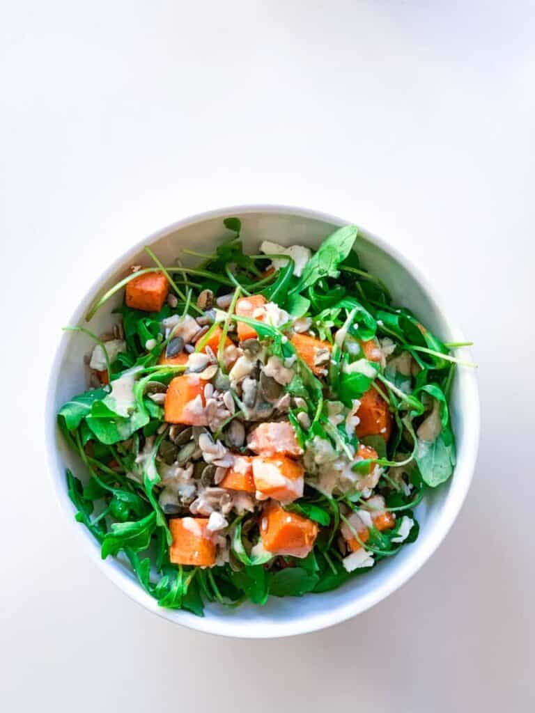 top view of a white bowl with roasted sweet potato and feta cheese salad topped with pumpkin seeds, sunflower seeds and tahini sauce