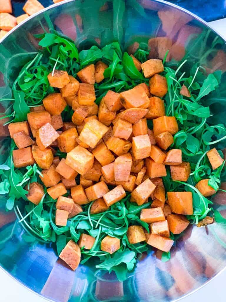 top view of arugula and roasted sweet potato in a large bowl
