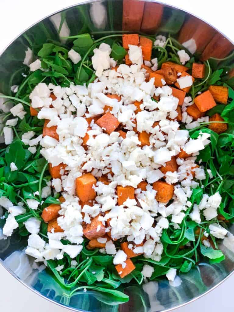 top view of arugula, roasted sweet potato and feta cheese in a large bowl