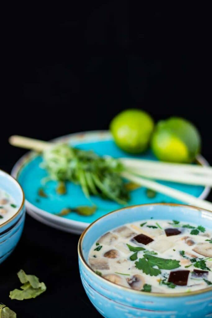 thai ginger coconut soup in a blue bowl with lemongrass and lime in the background