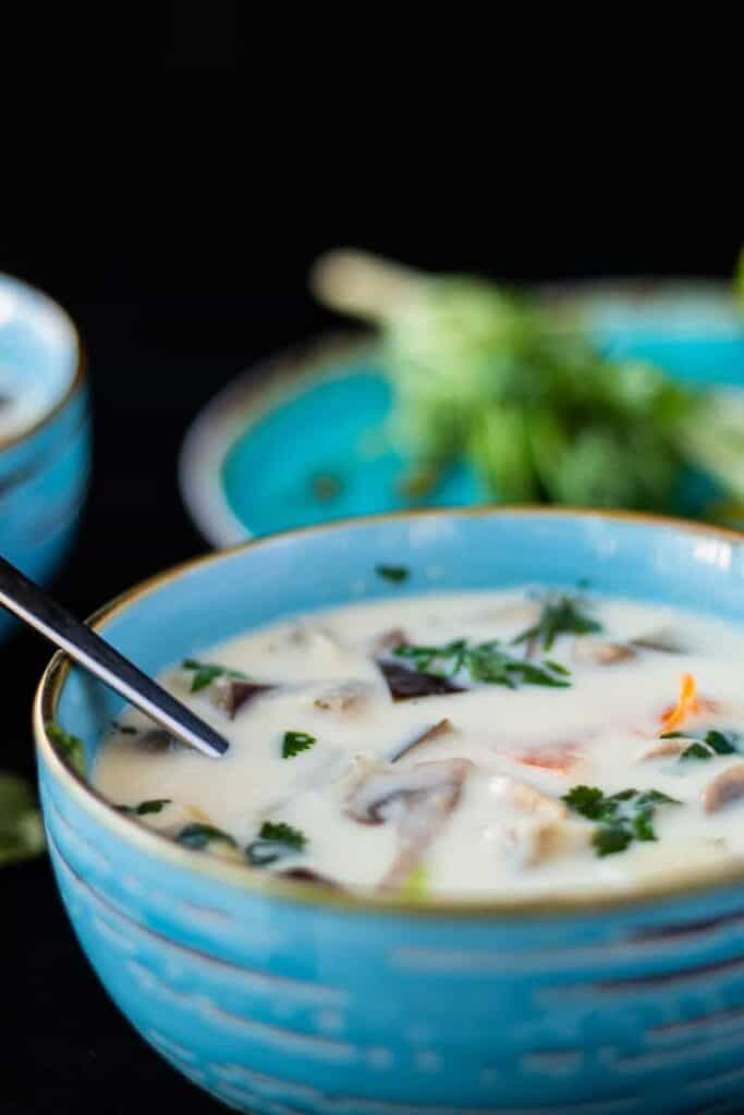 close up side view of thai ginger coconut soup in a blue bowl