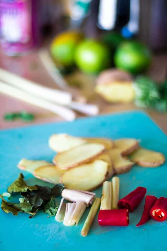 sliced ginger, lime leaves, lemon grass and chili on a blue chopping board