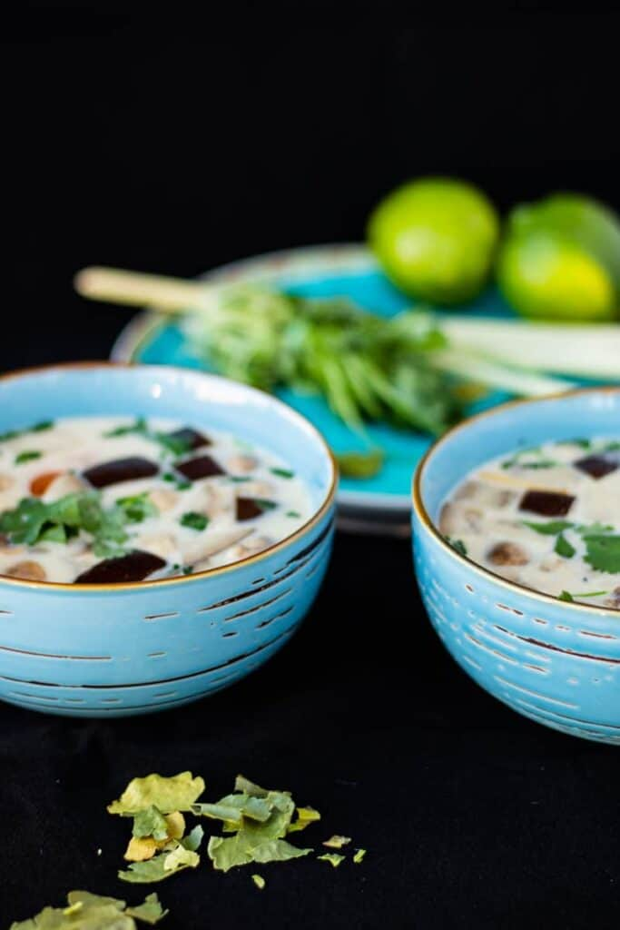 two blue bowls of thai ginger coconut soup on a black surface