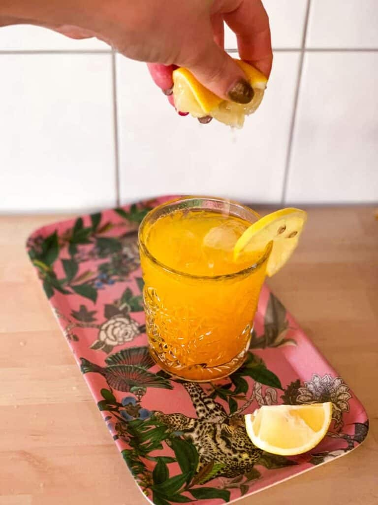 the resolution keeper non-alcoholic detox cocktail in a glass with a lemon slice, with lemon being squeezed into it