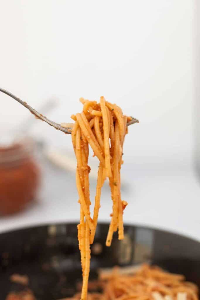 side view of a fork with red pesto pasta