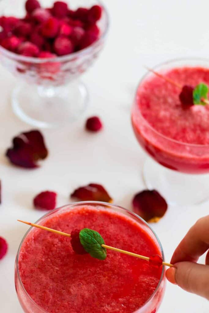 a glass of sparkling raspberry grapefruit mocktail  being decorated