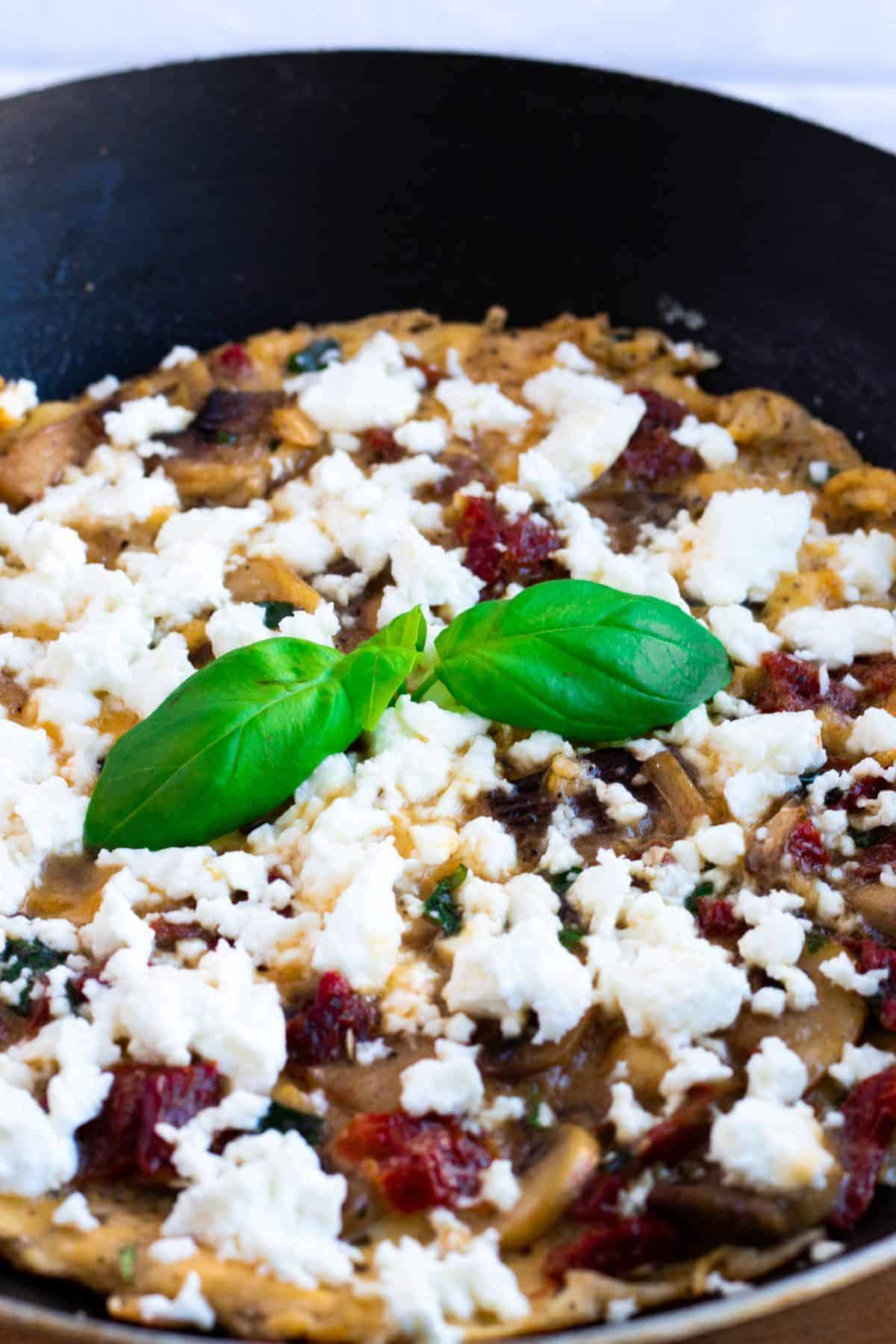 close-up of a breakfast frittata with feta cheese, mushrooms and sun-dried tomatoes in a pan