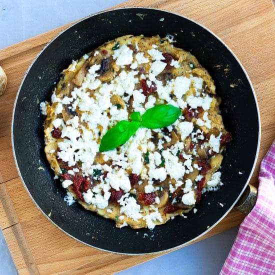top view of a breakfast frittata with feta cheese, mushrooms and sun-dried tomatoes in a pan on a wooden chopping board