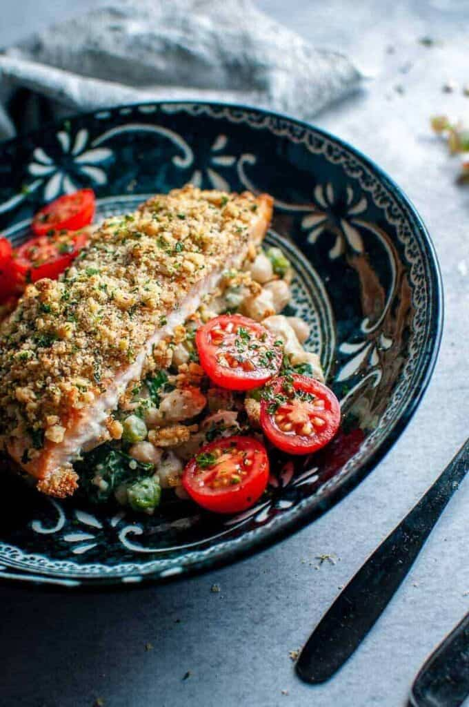 walnut crusted salmon in a dark bowl with cherry tomatoes