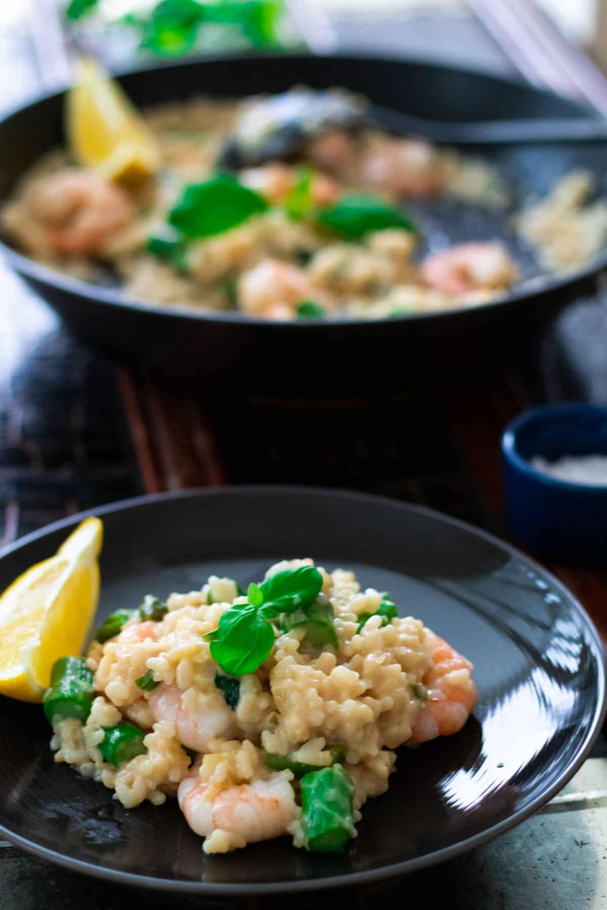 a plate with shrimp risotto in front of a a pan of shrimp risotto