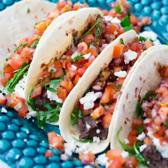 close-up of four vegetarian tacos with black beans, feta cheese and pico de gallo