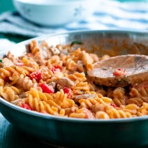 close up of creamy chicken pasta with feta cheese, basil and cherry tomatoes in a pan
