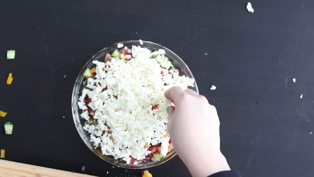 topping shopska salad with shredded feta cheese