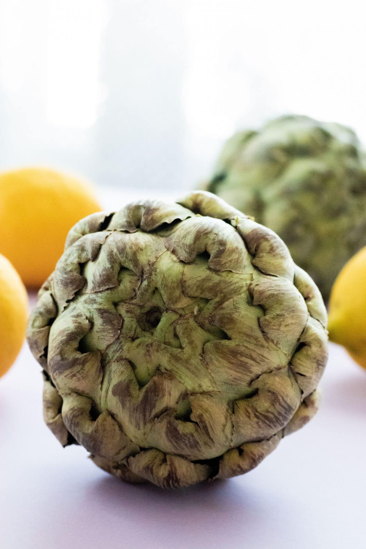 an artichoke with another artichoke and lemons in the background, on a lavender surface