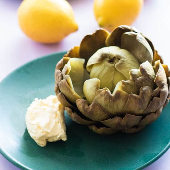 boiled artichoke with whipped lemon butter on a green plate