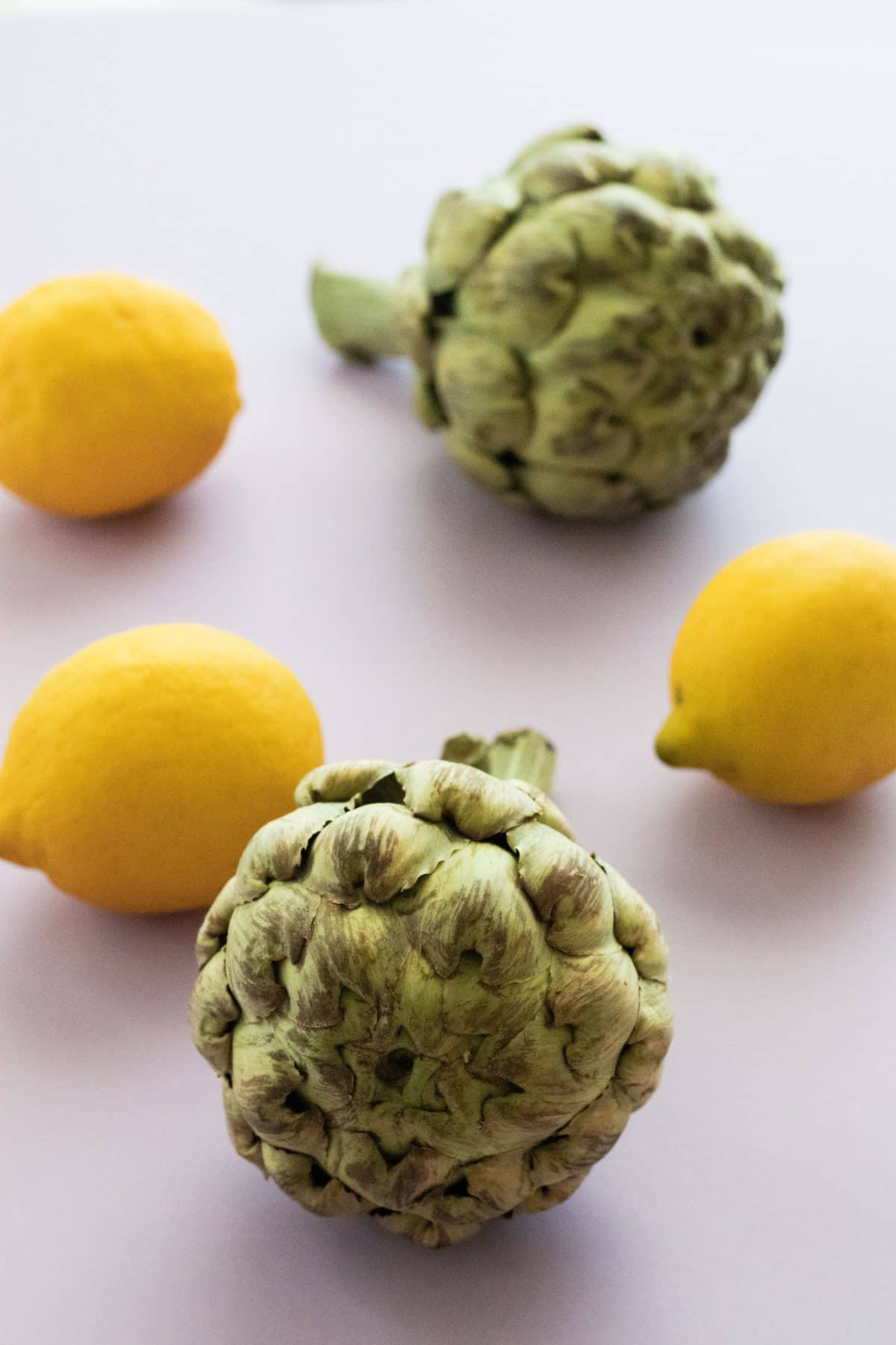 two artichokes and three lemons on a lavender surface