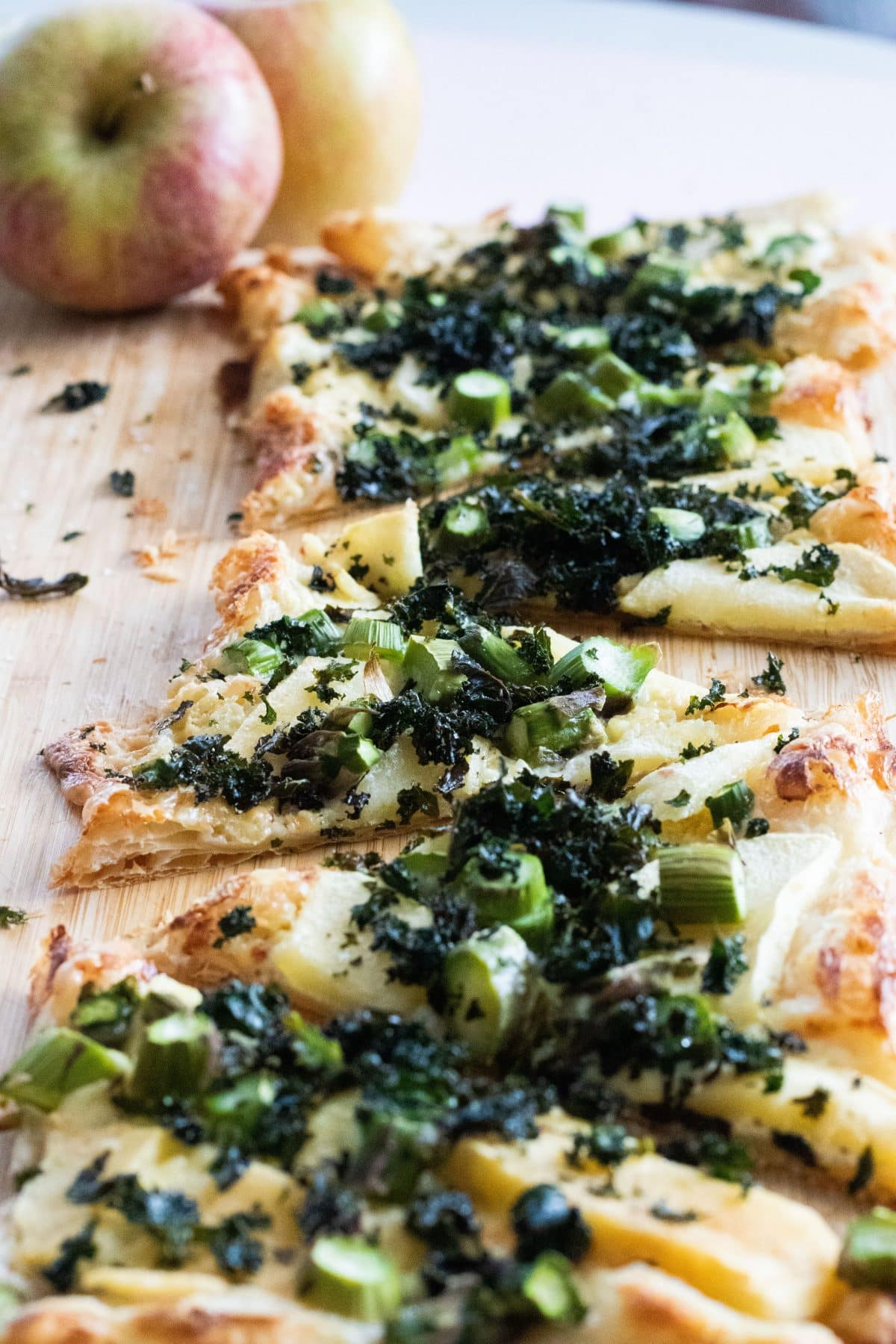 close-up of puff pastry pizza with blue cheese, apples and kale chips