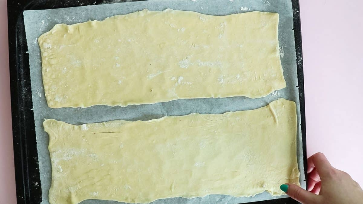 processshot - puff pastry dough rolled out onto parchment paper