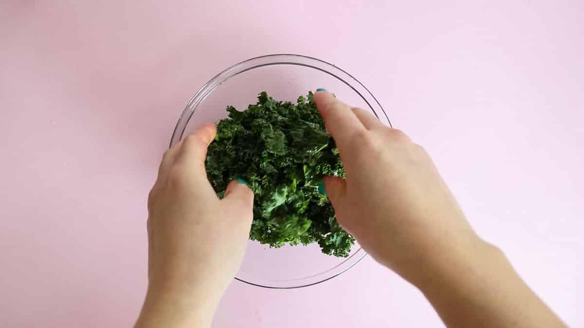 process shot - massaging kale for kale chips