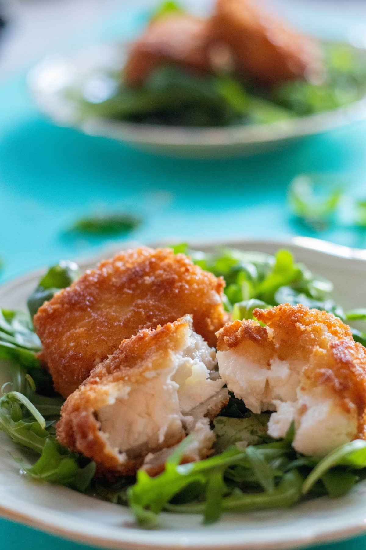 panko breaded feta cheese on a bed of greens with one breaded cheese split open