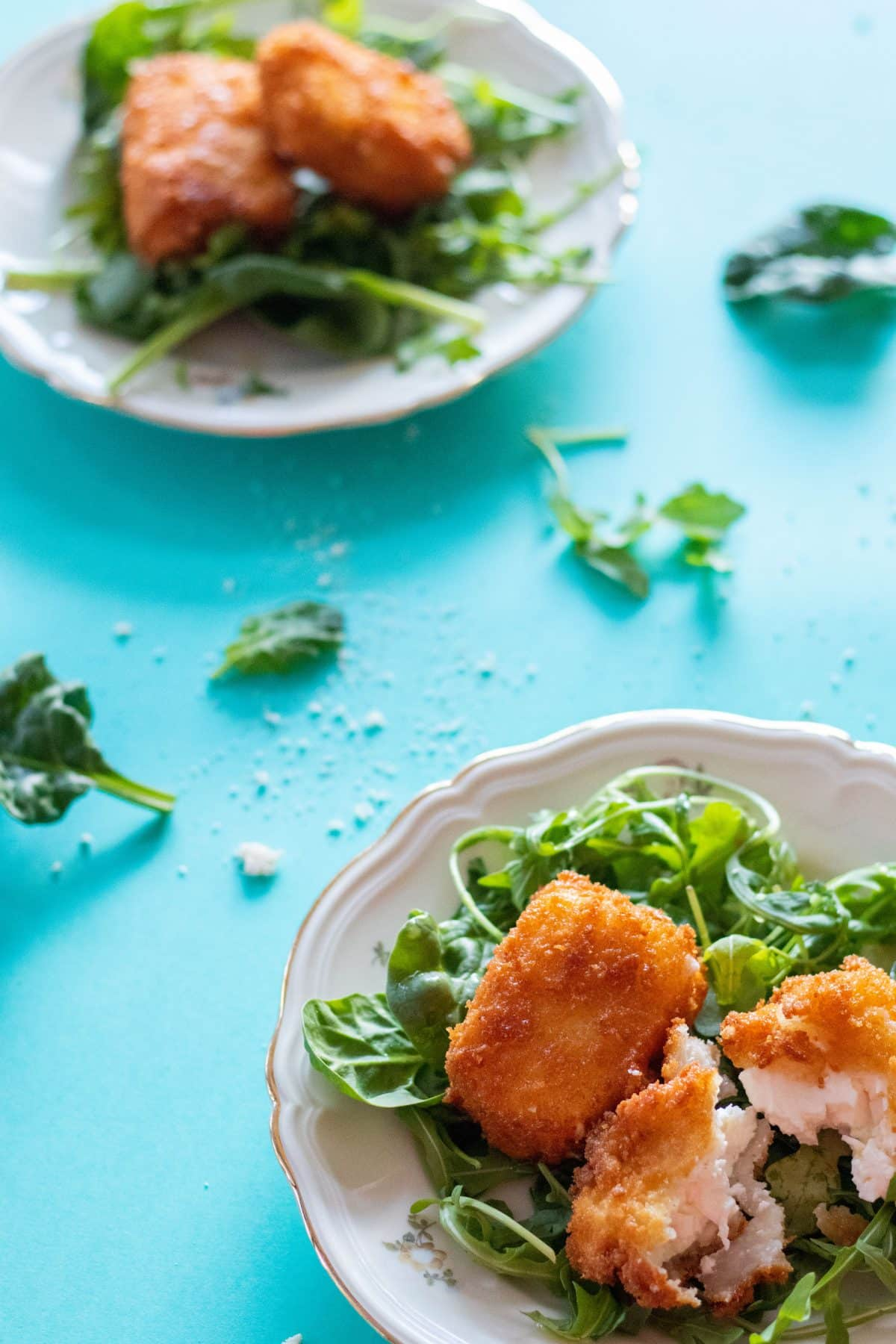 top view of panko breaded feta cheese on a bed of greens on a plate on a turquoise background