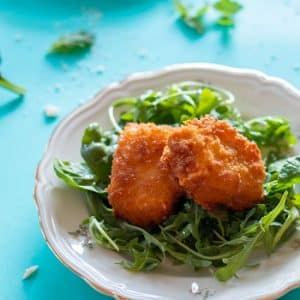 two pieces of panko crusted feta cheese on a bed of greens on a plate, on a turquoise background
