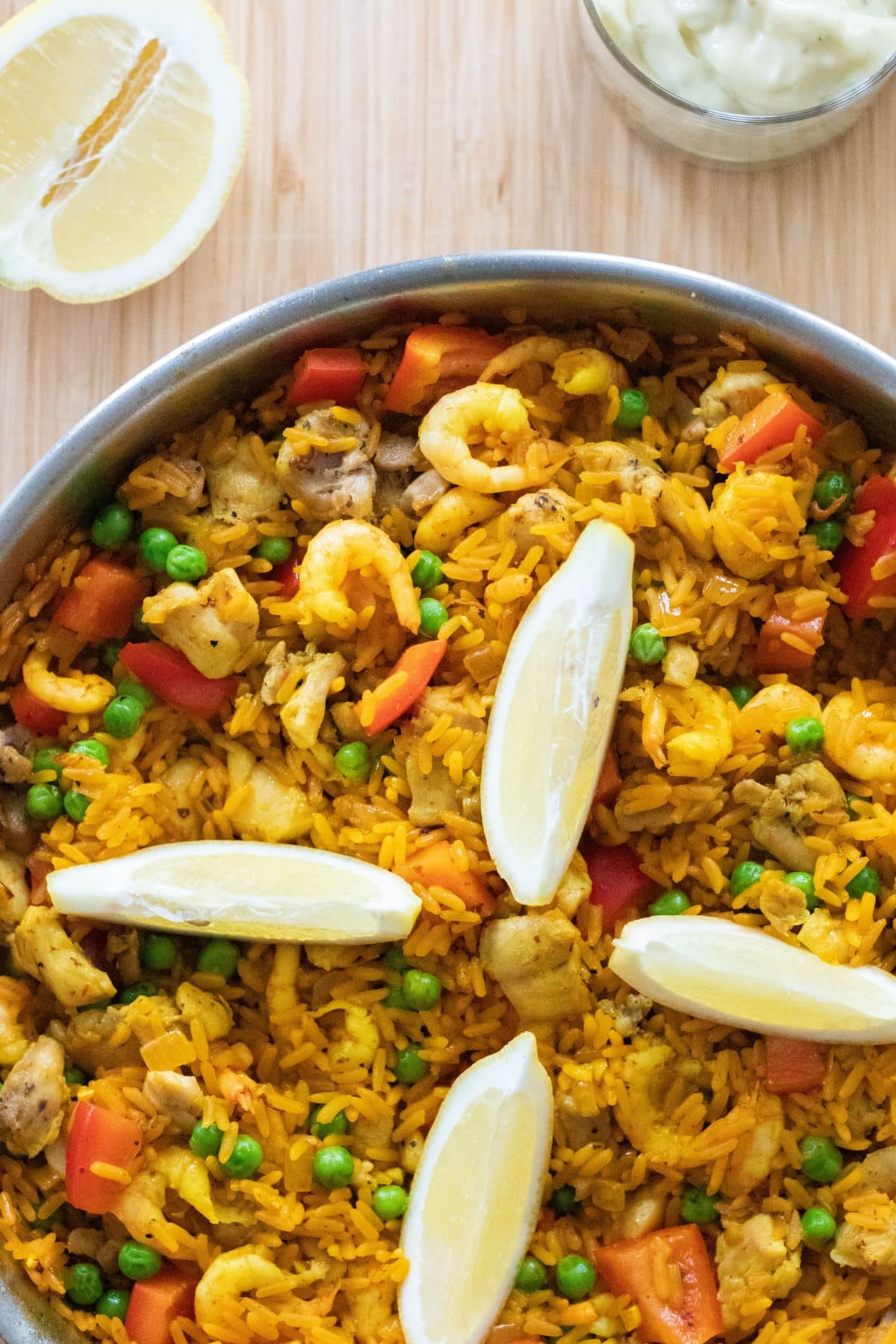close up top down photo of paella with lemon wedges