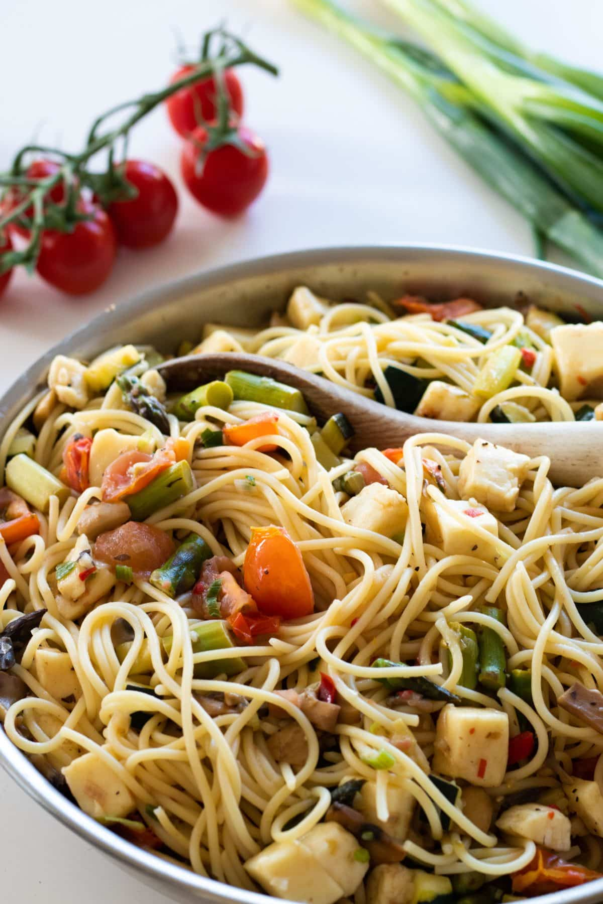 sideview of pasta primavera in a pan with a wooden spoon, cherry tomatoes and spring onions in the background