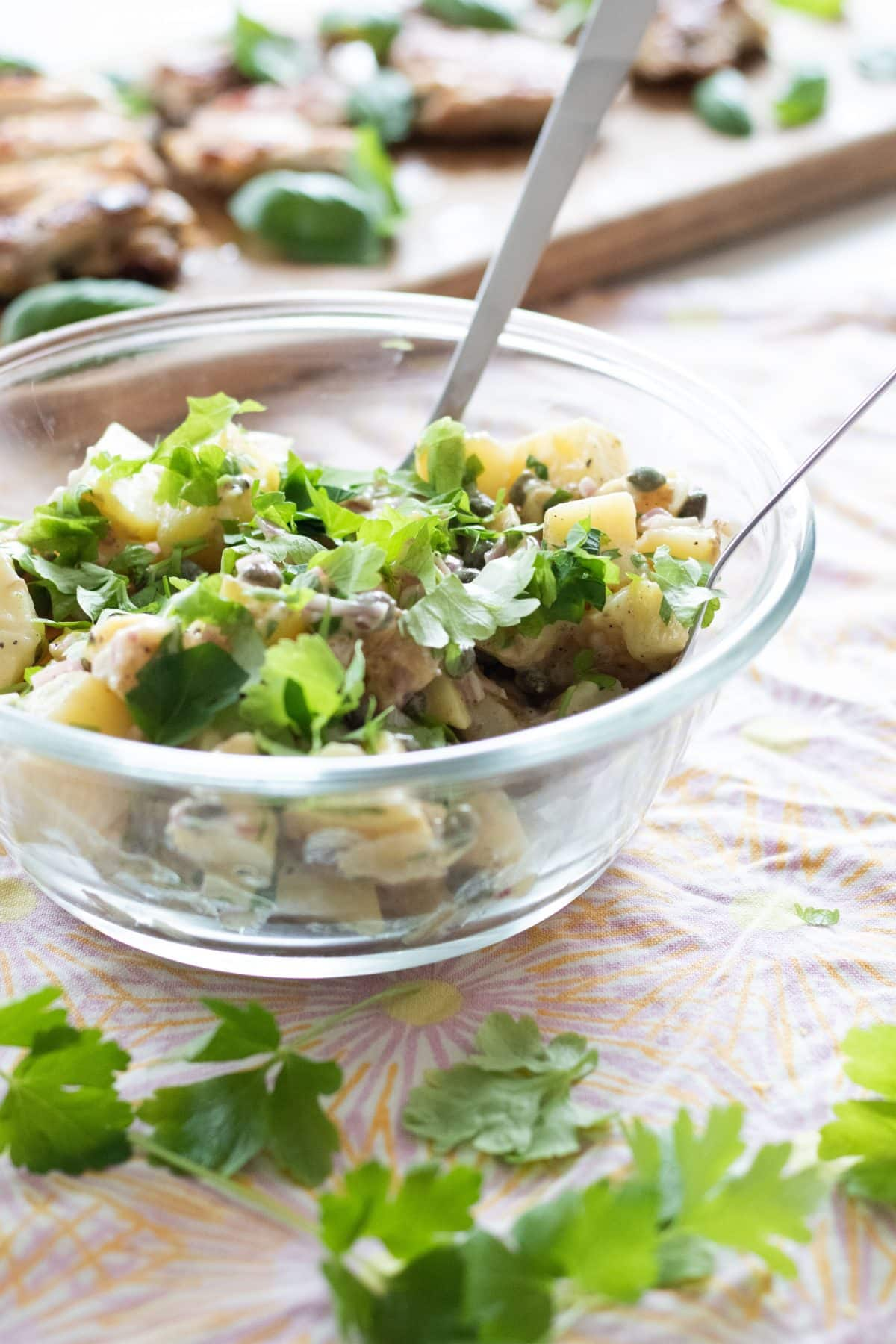 side view of french potato salad with parsley and capers
