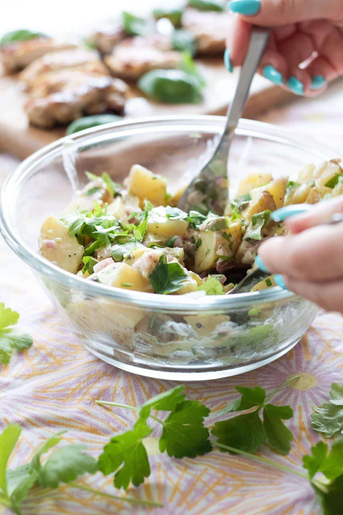 mixing together a potato salad with a knife and spoon