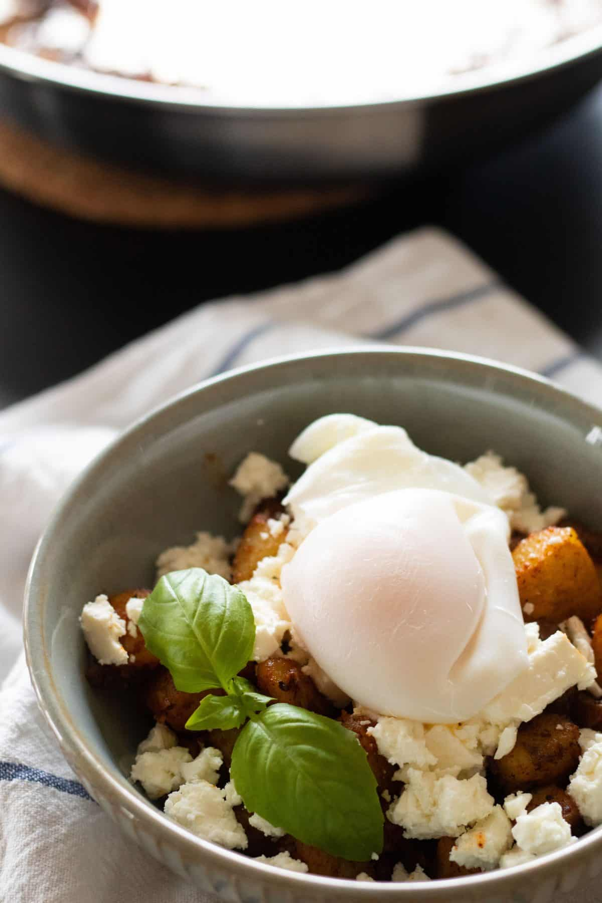 side view of a bowl with fried potatoes, feta cheese and a poached egg