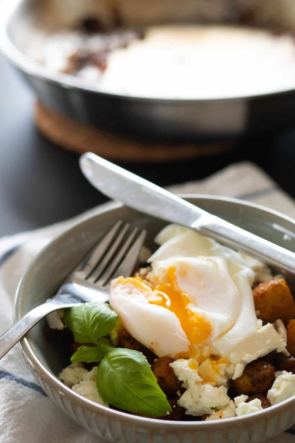 closeup sideview of a bowl with fried potatoes, feta cheese and poached egg