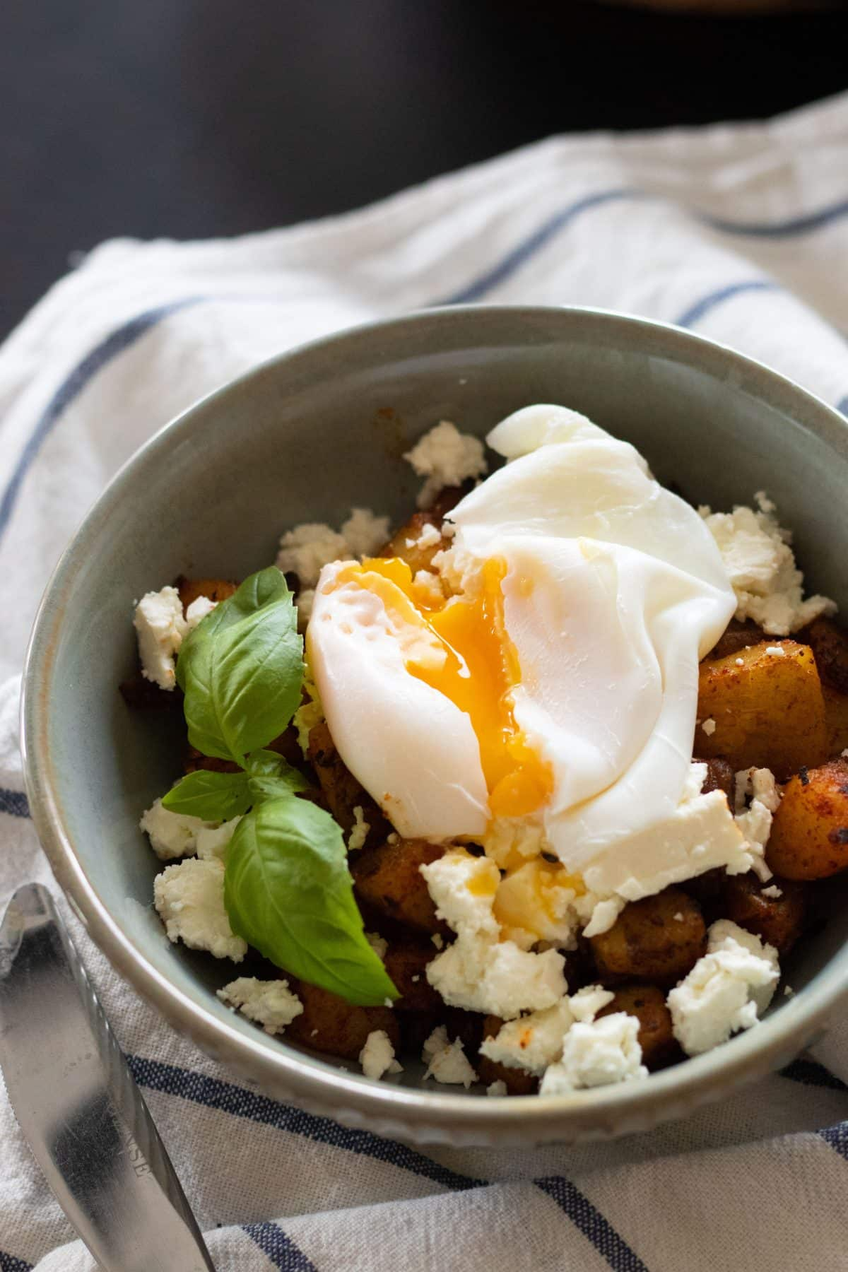 top view of a bowl of fried potatoes with feta cheese and a poached egg with the yolk running out