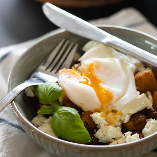 closeup sideview of a bowl with fried potatoes, feta cheese, poached egg and a sprig of basil