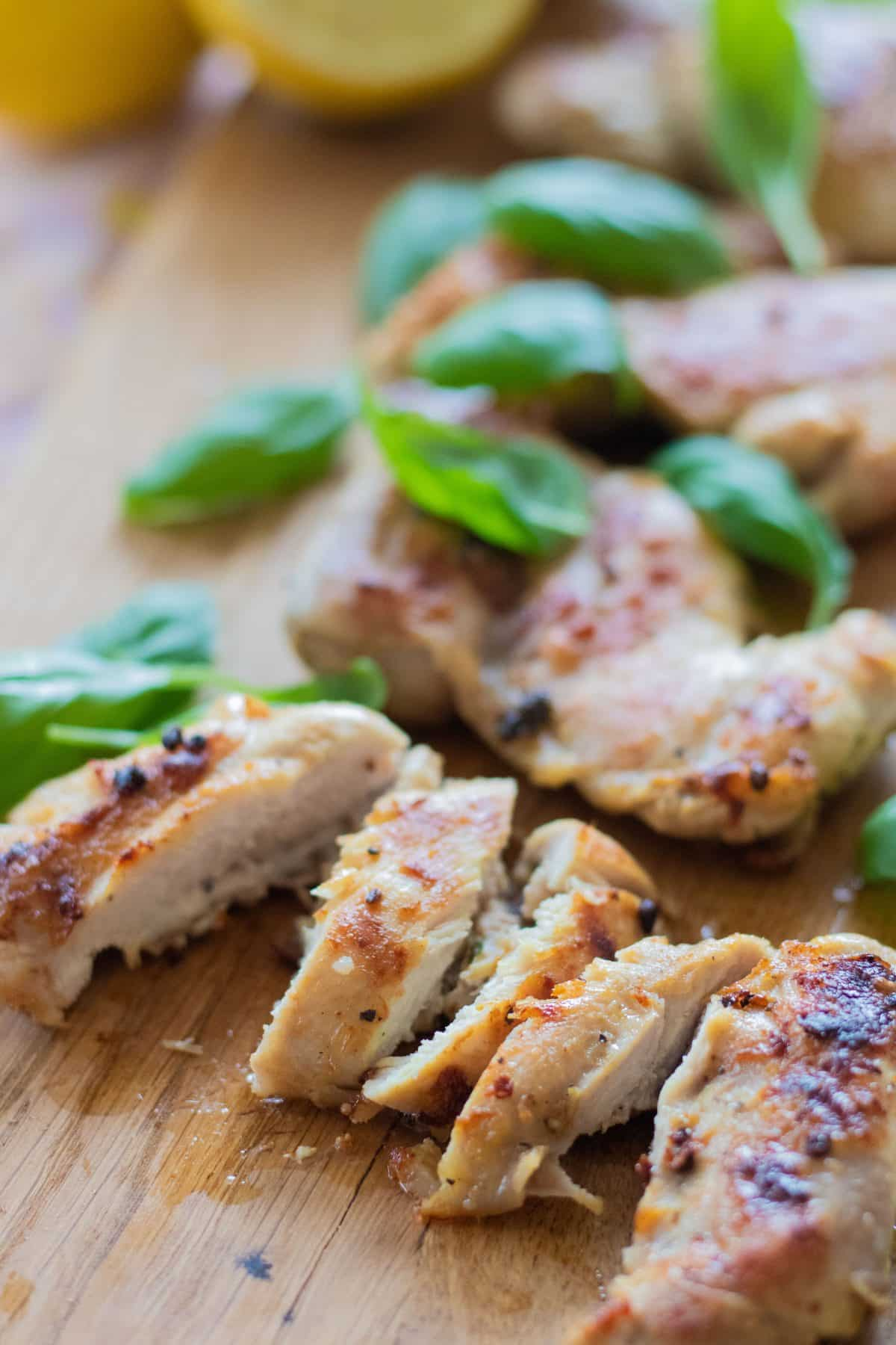 sideview of sliced grilled chicken marinated with lemon and decorated with basil leaves
