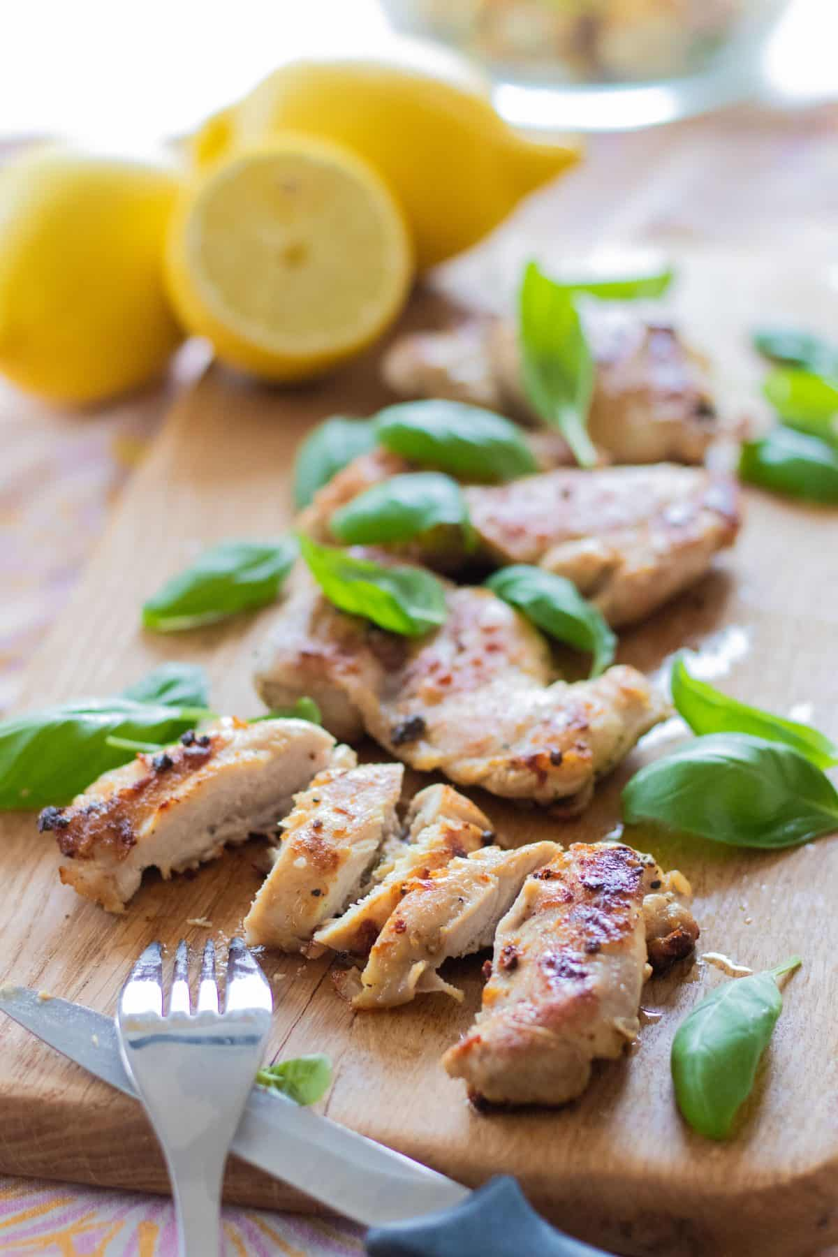sideview of sliced grilled lemon marinated chicken with basil leaves and a knife and fork