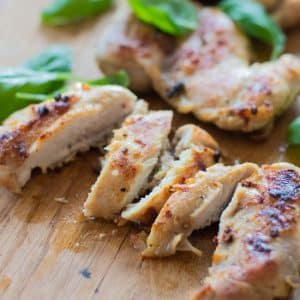 closeup of sliced grilled chicken with basil leaves