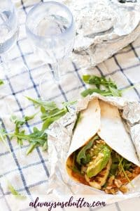 wrap with halloumi, avocado and arugula and two plastic wine glasses with water on top of a checkered picnic blanket