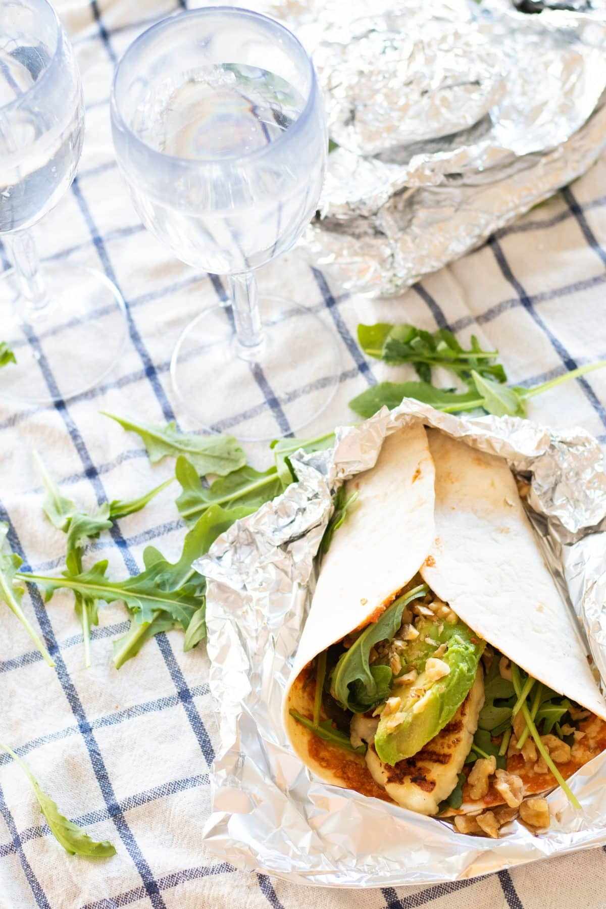 a halloumi wrap and two plastic wine glasses with water on top of a checkered picnic blanket