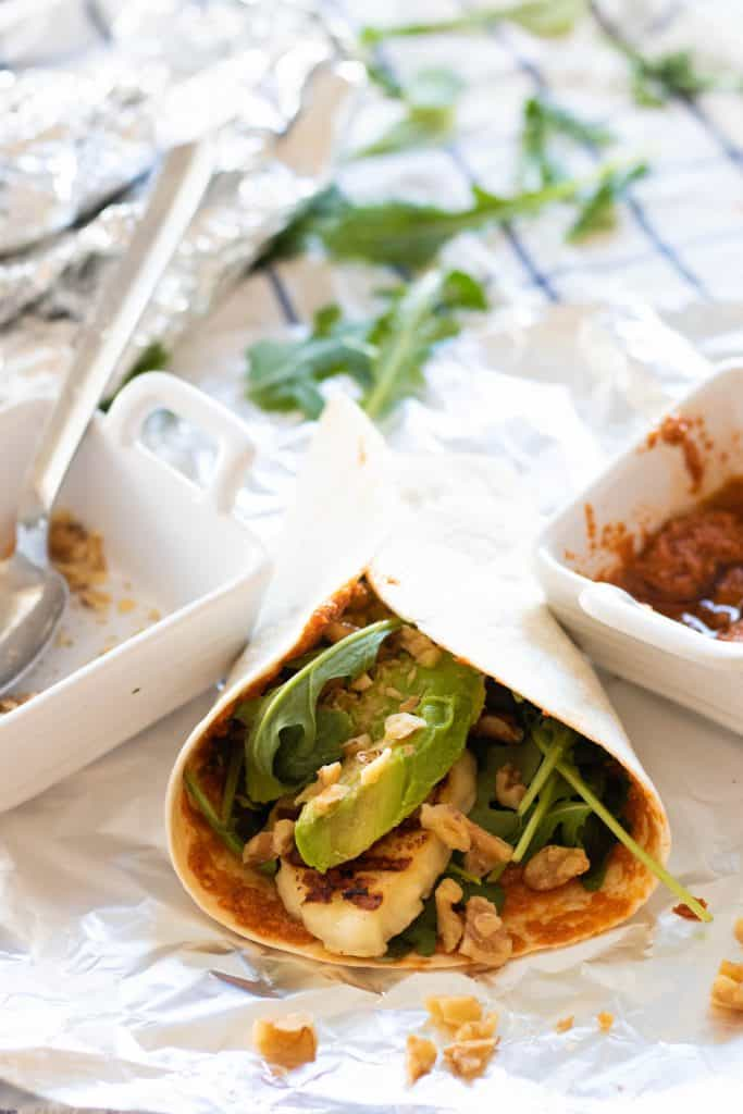 wrap with halloumi, avocado and arugula and two small square bowls on top of a checkered cloth