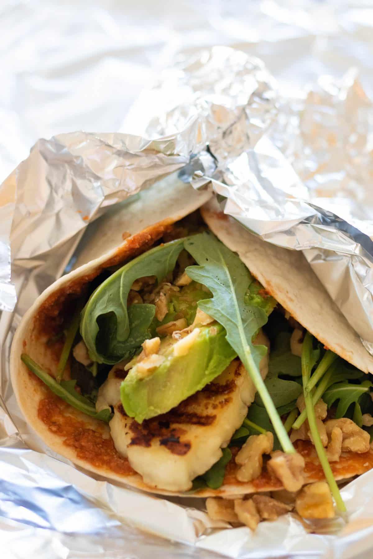 close up of wrap with halloumi, avocado and arugula in aluminium foil