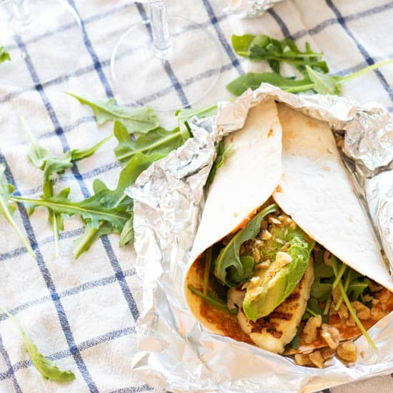 wrap with halloumi, avocado and arugula on top of a checkered picnic blanket